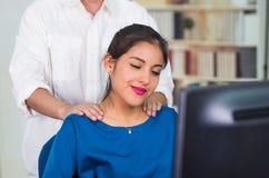 Aantrekkelijke donkerbruine bureauvrouw die blauwe sweaterzitting dragen door bureau die schoudermassage, het concept van de span Royalty-vrije Stock Afbeelding