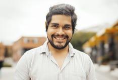 Aantrekkelijke donkerbruine Latijnse mens die de camera en het glimlachen bekijken stock fotografie