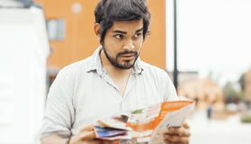Aantrekkelijke donkerbruine Latijnse mens die opzij en de kaart houden kijken stock fotografie