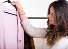 Aantrekkelijke donkerbruine status die door kleren op kledingsrek kijken, het winkelen manierconcept Stock Foto