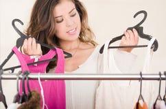Aantrekkelijke donkerbruine status met hoofd binnen - tussen kleren bij kledingsrek, het winkelen manierconcept Royalty-vrije Stock Foto