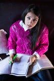 Aantrekkelijke donkerbruine studentelezing die in haar girly ruimte bestuderen Royalty-vrije Stock Foto's