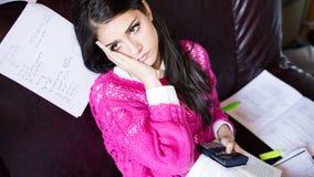 Aantrekkelijke donkerbruine studentelezing die in haar girly ruimte bestuderen Royalty-vrije Stock Foto