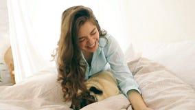 Aantrekkelijke donkerbruine vrouw in bed die selfie met haar kleine hondpug nemen Videolengte De goede stemming van de weekendoch stock footage