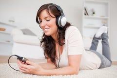 Aantrekkelijke donkerbruine vrouw die aan muziek luistert Royalty-vrije Stock Afbeelding