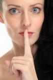 Aantrekkelijke donkerbruine vrouw die de vinger voor haar lippen plaatsen op witte achtergrond Stock Foto