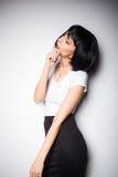 Aantrekkelijke donkerbruine vrouw die zich naast een muur bevinden Royalty-vrije Stock Fotografie