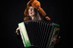 Aantrekkelijke emotionele vrouw die in bonthoed de harmonika spelen stock foto