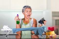 Aantrekkelijke en beklemtoonde Aziatische midden oude dame die thuis keuken het wanhopige en overweldigde ongelukkig voelen strij royalty-vrije stock foto