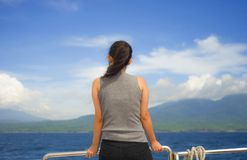 Aantrekkelijke en gelukkige Aziatische Chinese vrouw op excursieschip of veerboot oceaan en eiland die van zeebries op de zomerva stock afbeeldingen