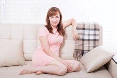 Aantrekkelijke en mooie midden oude vrouwenzitting op bank en thuis het ontspannen menopause Stock Foto