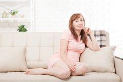 Aantrekkelijke en mooie midden oude vrouwenzitting op bank en thuis het ontspannen menopause Stock Foto's