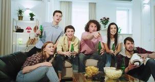 Aantrekkelijke en opgewekte vrienden die lettend op een voetbalwedstrijd op voorzijde van TV zij zeer het enthousiaste schreeuwen stock videobeelden