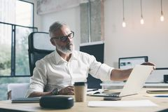 Aantrekkelijke en vertrouwelijke volwassen zakenman die mobiele laptop computer met behulp van terwijl het werken bij de houten l royalty-vrije stock foto's