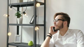 Aantrekkelijke Europese kerel die op telefoon spreken terwijl het gebruiken van laptop bij werkplaatsjaren '20 4k stock video