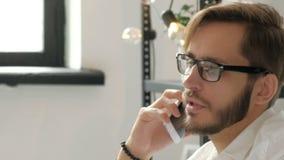 Aantrekkelijke Europese kerel die op telefoon spreken terwijl het gebruiken van laptop bij werkplaatsjaren '20 4k stock videobeelden