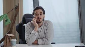 Aantrekkelijke Europese kerel die op telefoon spreken terwijl het gebruiken van smartphone op het werk stock footage