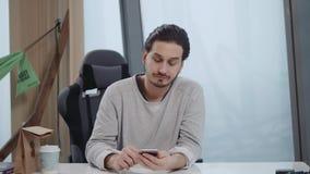 Aantrekkelijke Europese kerel die op telefoon spreken terwijl het gebruiken van smartphone op het werk stock video