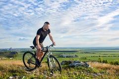 Aantrekkelijke fietser die de fiets berijden op de mooie de zomerberg tril Stock Fotografie