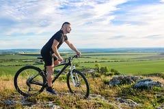 Aantrekkelijke fietser die de fiets berijden op de mooie de zomerberg tril Royalty-vrije Stock Fotografie