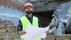 Aantrekkelijke gebaarde bouwer in oranje helm op vernietigde de bouwachtergrond Ernstige bouwer die tekening analyseren stock video
