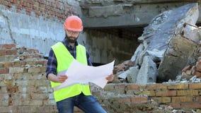 Aantrekkelijke gebaarde bouwer in oranje helm op vernietigde de bouwachtergrond Ernstige bouwer die tekening analyseren stock footage