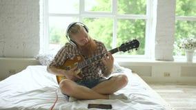 Aantrekkelijke gebaarde mens die in hoofdtelefoons op bed zitten die leren gitaar te spelen die tabletcomputer in moderne slaapka stock videobeelden