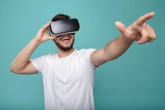 Aantrekkelijke gebaarde mens die VR-hoofdtelefoon proberen en vinger poniting Jonge mens die een andere wereld met virtuele werke royalty-vrije stock afbeeldingen
