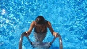 Aantrekkelijke gelooide vrouw in zwempak die van pool weggaan Jong sexy meisje die de zomervakantie van het verfrissen in bassin  stock videobeelden