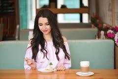 Aantrekkelijke gelukkige jonge vrouwenzitting en het eten van dessert in koffie stock fotografie