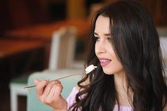Aantrekkelijke gelukkige jonge vrouwenzitting en het eten van dessert in koffie royalty-vrije stock afbeelding