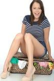 Aantrekkelijke Gelukkige Jonge vrouwenzitting op een Ingepakte Overlopende Koffer Stock Afbeeldingen