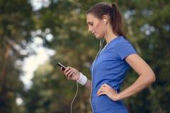 Aantrekkelijke gelukkige vrouw status die aan muziek luisteren Royalty-vrije Stock Foto's