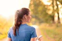 Aantrekkelijke gelukkige vrouw status die aan muziek luisteren Royalty-vrije Stock Afbeelding