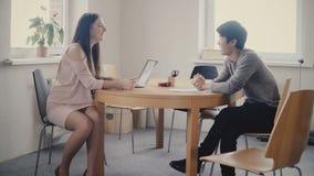 Aantrekkelijke gelukkige vrouwelijke leider die aan Aziatische mannelijke collega luisteren Het gemengde het behoren tot een bepa stock videobeelden