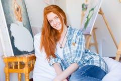 Aantrekkelijke gelukkige vrouwenzitting op witte beanbag in kunstworkshop stock fotografie