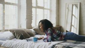 Aantrekkelijke gemengde rastiener die gebruikend laptop voor het delen van sociale media die in bed thuis liggen lauging Royalty-vrije Stock Foto's