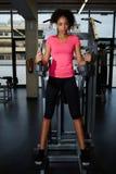 Aantrekkelijke geschikte vrouw in roze t-shirt die een rust na training hebben bij gymnastiek royalty-vrije stock fotografie