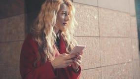 Aantrekkelijke gir die sms gebruikend app op slimme telefoon texting Het bedrijfsvrouwenverblijf dichtbij commercieel centrum en  stock footage