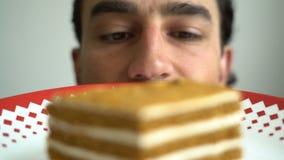 Aantrekkelijke glimlachende jonge donkerbruine mens die cake op hartstocht van plaat de smakelijke koekjes aan zoete unhealhy voe stock footage