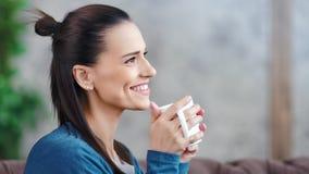 Aantrekkelijke glimlachende jonge donkerbruine vrouw die en heet drank middelgroot close-up dromen drinken stock footage