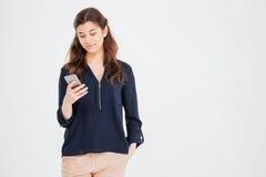 Aantrekkelijke glimlachende jonge vrouw die en smartphone bevinden zich gebruiken royalty-vrije stock foto