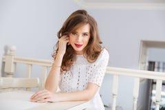 Aantrekkelijke glimlachende jonge vrouw in witte kleding bij koffie stock foto