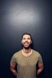 Aantrekkelijke, glimlachende mens die tegen de muur leunen Stock Foto's