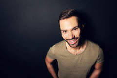 Aantrekkelijke, glimlachende mens die zich naast een muur bevinden Royalty-vrije Stock Foto