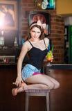 Aantrekkelijke glimlachende pinup vrouw die in denimborrels op barkruk en het drinken limonade zitten Stock Afbeelding