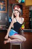 Aantrekkelijke glimlachende pinup vrouw die in denimborrels op barkruk en het drinken limonade zitten Stock Afbeeldingen