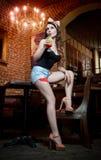Aantrekkelijke glimlachende pinup vrouw die in denimborrels op barkruk en het drinken limonade zitten Royalty-vrije Stock Fotografie