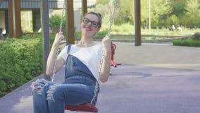 Aantrekkelijke glimlachende vrouw die op speelplaats slingeren stock video