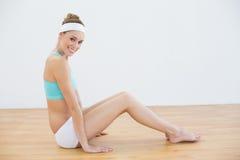 Aantrekkelijke glimlachende vrouw die sportkledingszitting op vloer in sporthal dragen Royalty-vrije Stock Foto's